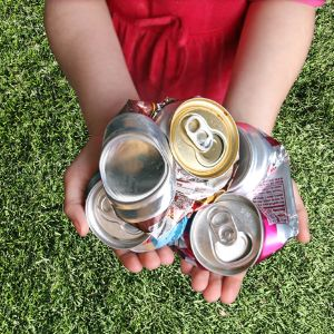 Child holding aluminum cans picked up for recycling