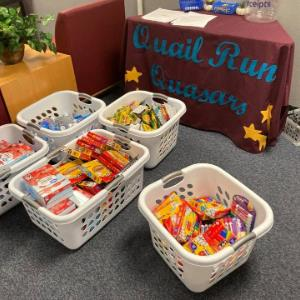 Baskets of school supplies with water, markers, crayons, ziplock plastic bags and more