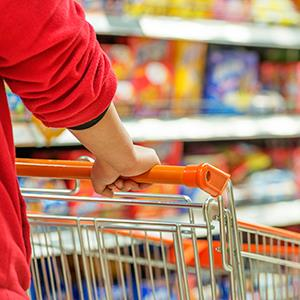 Shopping cart in store aisle with groceries on shelves.