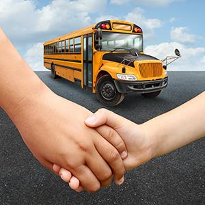 IMAGE: Children holding hands in front of a school bus.