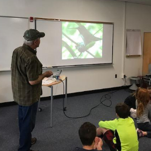 Member of Audubon shows slide with native bird to students
