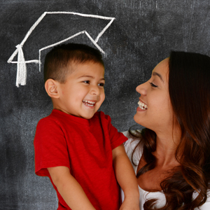 IMAGE: Young boy with mom standing in front of blackboard with graduation cap.