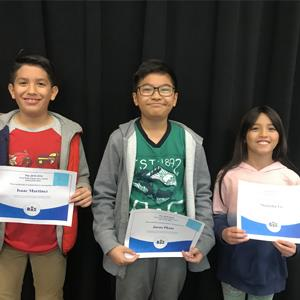 Spelling bee students holding certificates