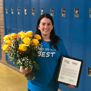 IMAGE: Megan Hawkes recognized by Tucson Values Teachers holding certificate and flowers.