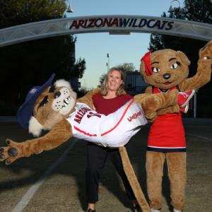 IMAGE:  Jill Hurst lifting UofA Mascot Wilbur Wildcat, with Wilma Wildcat by her side.