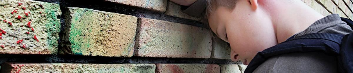 Sad child against brick wall