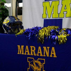 Football helmet and blue and gold pom-poms on signing table