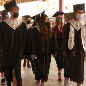 MVHS Seniors walking at Tortolita Middle School is cap & gown
