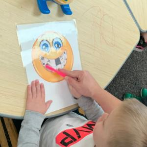 IMAGE: Preschooler brushing teeth of a happy emoji on paper.