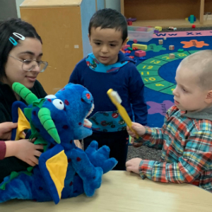 IMAGE: Preschooler holding large toothbrush and brushing teeth of stuffed dinosaur.