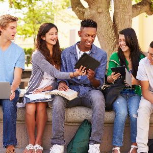 Students sitting together outside looking at a mobile device and books.