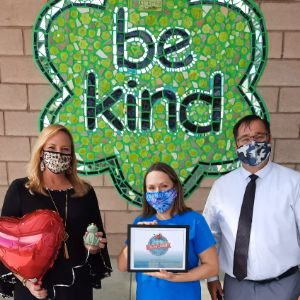 Principal holding Hulafrog and being awarded in front of BeKind wall mural