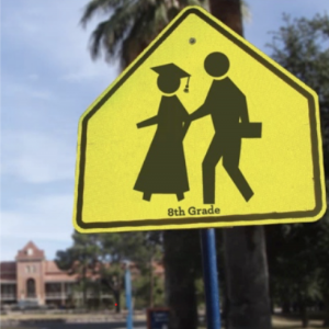 Road sign depicting students with grad cap and briefcase in crosswalk