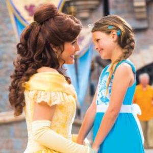 IMAGE: Disney Princess Belle with visiting child at a Disneyland park.