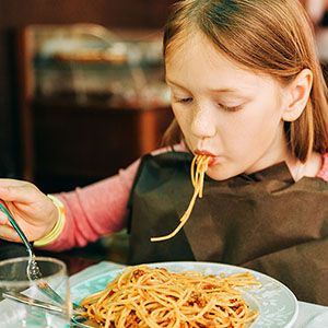 Young girl eating spaghetti