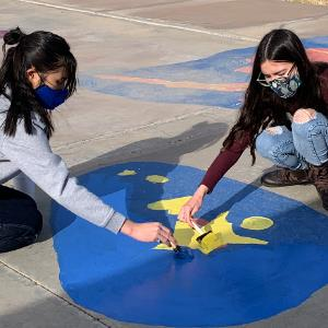 Students repainting images on the Twin Peaks Peaceful Playground