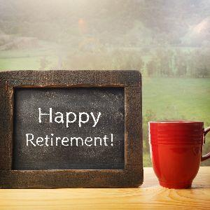 Red coffee cup with chalkboard sign wishing happy retirement, sitting on wood countertop