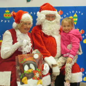 IMAGE: An MUSD student is held by Santa while Mrs. Claus shows gift bag.