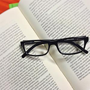 IMAGE: Textbook with reading glasses.