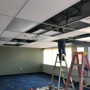 IMAGE: An MUSD Electrician installs lighting in renovated MCAT classrooms.