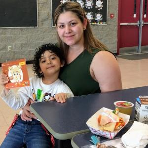 IMAGE: A parent with a child enjoying lunch at Quail Run Elementary school.