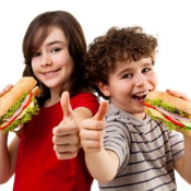 IMAGE: Female and male students eating a sub sandwich and giving a thumbs up.