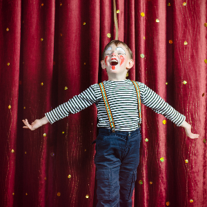 Child performing in a drama production in front of a curtain