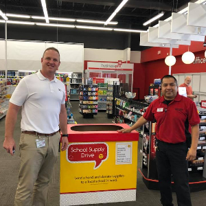 Butterfield Principal and Office Depot Manager stand in front of school supply drive box