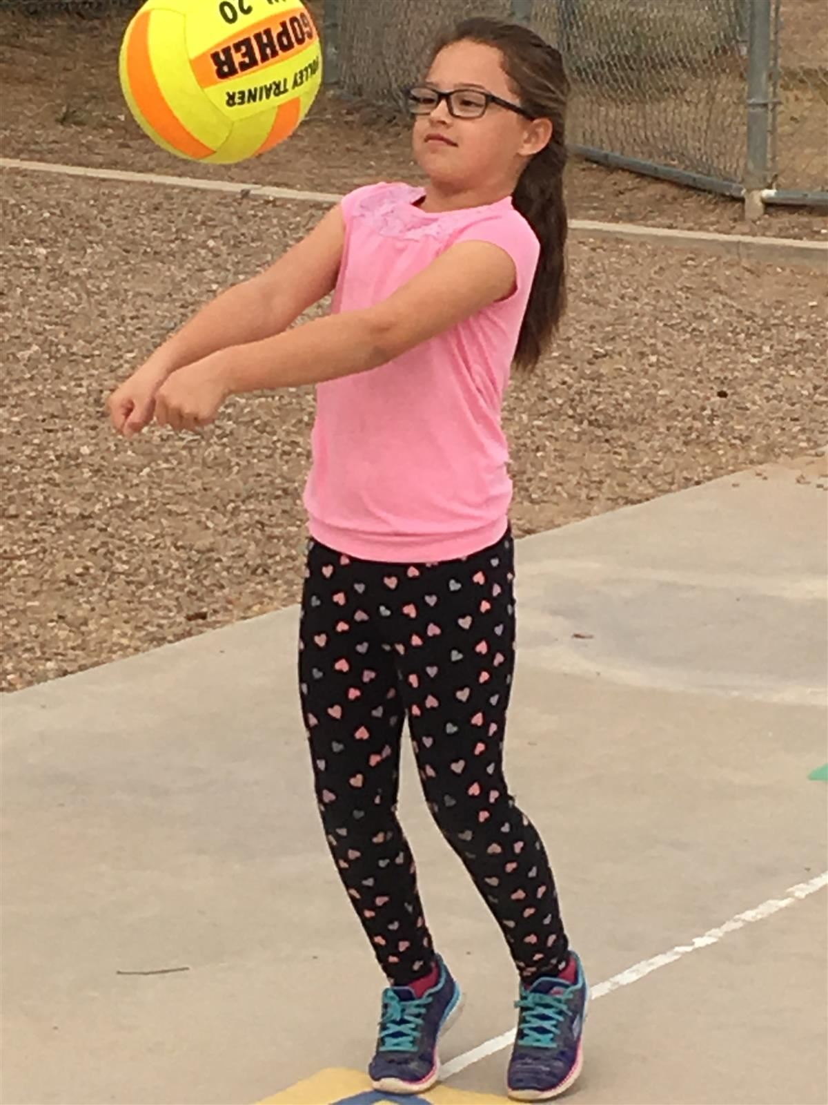Little adorable girl playing beach volleyball with ball