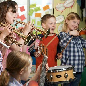 IMAGE: Students participating in band with trumpets, drums, guitars and violins.