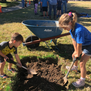 IMAGE: A young boy and girl dig a hole for a tree.