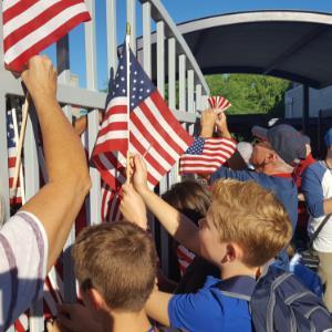 Students, parents and grandparents hang flags on fence for Patriot Day