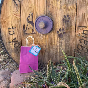 Teacher goodie bag sits on rock in front of wooden wheel inscribed with happy trails