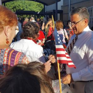 Principal Dan Johnson handing out flags on Patriot Day