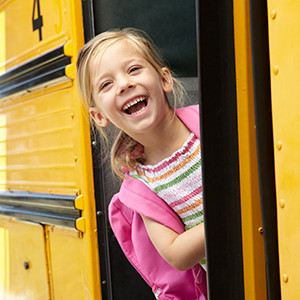 Girl leans out of bus door with big smile