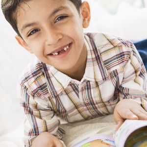Young boy reading and smiling